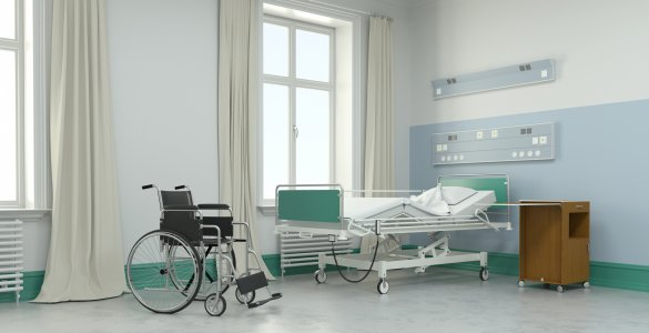 Leeres Krankenzimmer mit Bett und Rollstuhl im Pflegeheim