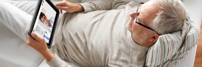 Mann auf Sofa mit Tablet in der Hand