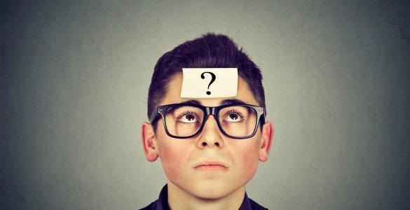 Junger Mann mit Post-it mit Fragezeichen auf der Stirn.