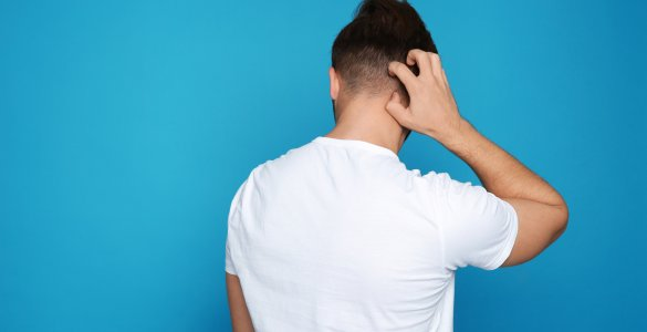 Mann kratzt sich am Hinterkopf.